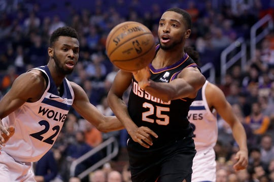 Phoenix Suns forward Mikal Bridges (25) passes around Minnesota Timberwolves forward Andrew Wiggins (22) during the second half of an NBA basketball game, Monday, Dec. 9, 2019, in Phoenix. (AP Photo/Matt York)