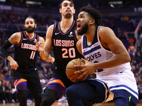 Minnesota Timberwolves center Karl-Anthony Towns (32) drives past Phoenix Suns forward Dario Saric (20) in the second half on Dec. 9, 2019 in Phoenix, Ariz.