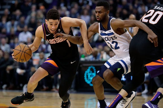 Phoenix Suns guard Devin Booker (1) drives around Minnesota Timberwolves forward Andrew Wiggins (22) during the second half of an NBA basketball game, Monday, Dec. 9, 2019, in Phoenix. (AP Photo/Matt York)
