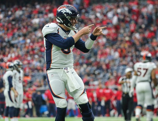 Broncos quarterback Drew Lock (3) celebrates after a touchdown by running back Phillip Lindsay during a game Dec. 8 against the Texans at NRG Stadium.