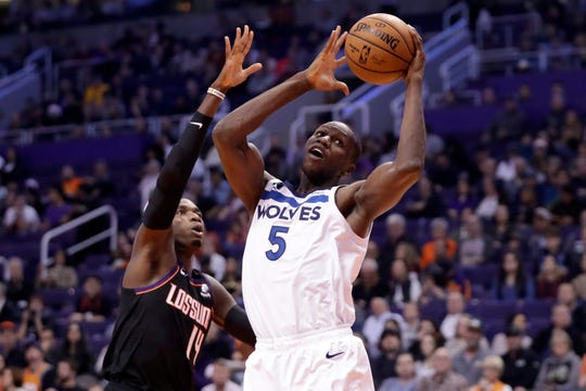 Minnesota Timberwolves center Gorgui Dieng (5) shoots as Phoenix Suns forward Cheick Diallo (14) defends during the first half of an NBA basketball game, Monday, Dec. 9, 2019, in Phoenix. (AP Photo/Matt York)