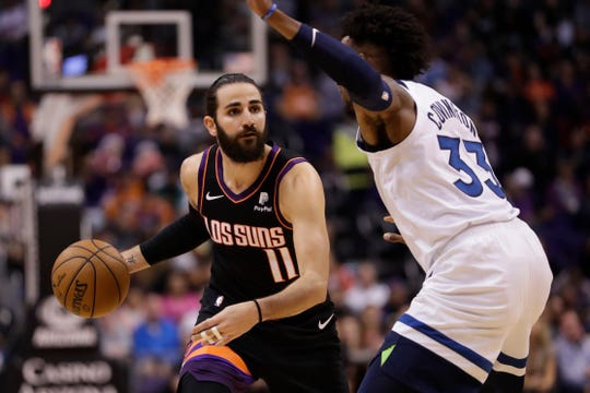 Phoenix Suns guard Ricky Rubio (11) looks to pass around Minnesota Timberwolves forward Robert Covington (33) during the second half of an NBA basketball game, Monday, Dec. 9, 2019, in Phoenix. (AP Photo/Matt York)