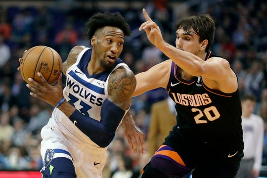 Minnesota Timberwolves forward Robert Covington (33) drives around Phoenix Suns forward Dario Saric (20) during the first half of an NBA basketball game, Monday, Dec. 9, 2019, in Phoenix. (AP Photo/Matt York)