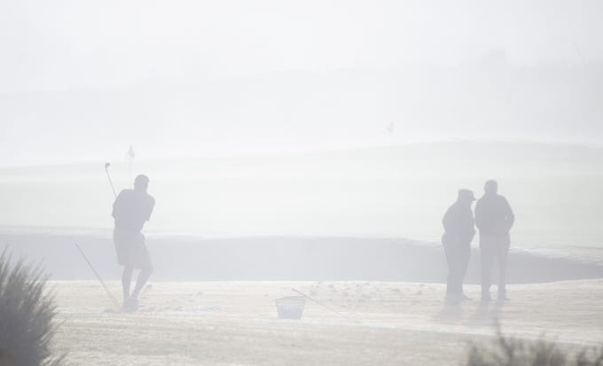 Golfers practice as fog hangs over the Whirlwind Golf Course at Wild Horse Pass on the Gila River Indian Community on Dec. 10, 2019.