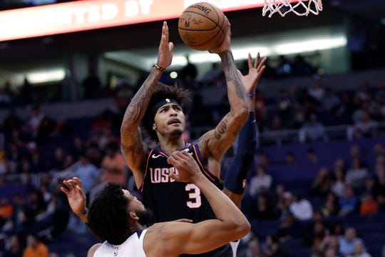 Phoenix Suns forward Kelly Oubre Jr. (3) shoots over Minnesota Timberwolves center Karl-Anthony Towns during the second half of an NBA basketball game, Monday, Dec. 9, 2019, in Phoenix. (AP Photo/Matt York)