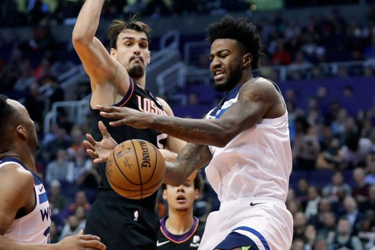 Minnesota Timberwolves forward Jordan Bell, right, loses the ball as Phoenix Suns forward Dario Saric defends during the first half of an NBA basketball game, Monday, Dec. 9, 2019, in Phoenix. (AP Photo/Matt York)
