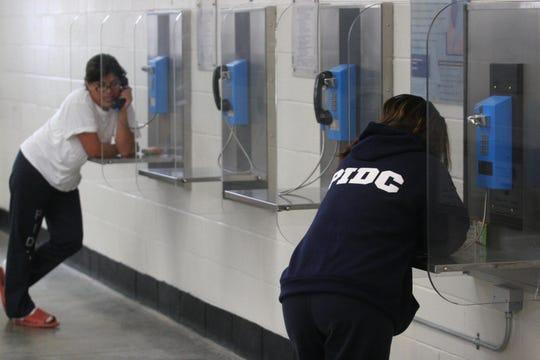 Detenidos en un centro de detención de Texas hacen uso de un teléfono directo gratuito.