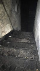 The attic stairs after the fire were blackened by the flames. The fire was mostly contained to the attic, but water and smoke damage affected the second-floor as well.