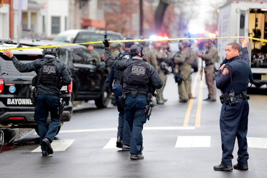 Port Authority Police officers arrive at the scene following reports of gunfire, Tuesday, Dec. 10, 2019, in Jersey City, N.J.  (AP Photo/Seth Wenig)