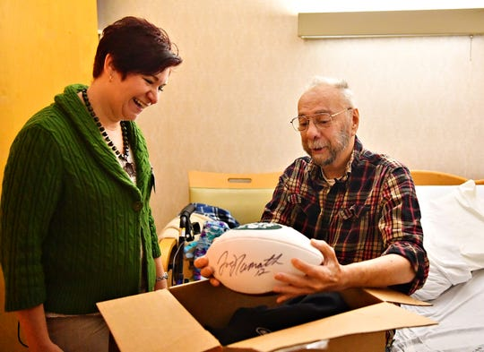 Heartland Hospice Administrator Christy Trump, left, looks on as patient Jack Snyder holds a football autographed by Joe Namath that Snyder received in a box full of New York Jets garb courtesy of the NFL team, at Manor Care Health Services - Kingston Court in Springettsbury Township, Tuesday, Dec. 10, 2019. Snyder, who was diagnosed with an untreatable form of lung cancer, has been a Jets fan since the early 1960's, and will be attending the New York Jets vs Baltimore Ravens game on Dec. 12, courtesy of the Heart's Desire Program, which gives Heartland Hospice patients the chance to fulfill their wishes. Dawn J. Sagert photo