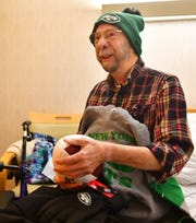 Heartland Hospice patient Jack Snyder receives a box full of New York Jets garb at Manor Care Health Services - Kingston Court in Springettsbury Township, Tuesday, Dec. 10, 2019. Snyder, who was diagnosed with an untreatable form of lung cancer, has been a Jets fan since the early 1960's, and will be attending the New York Jets vs Baltimore Ravens game on Dec. 12, courtesy of the Heart's Desire Program, which gives Heartland Hospice patients the chance to fulfill their wishes. Dawn J. Sagert photo