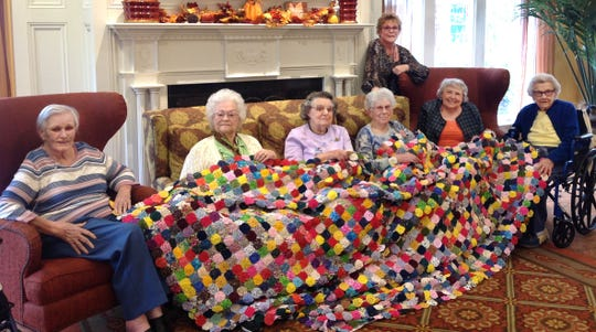 These six Country Meadows residents, led by Community Life Associate Diana Kistler, made this 7-by-8-foot quilt. They decided to put it up for auction to benefit the Alzheimer's Association, hoping to find a cure for the disease. From left to right, they are: Emma Statella, Liz Tomlinson, Beatrice Roth, the late Molly Sowers,  Joan Molesworth, and Roberta Throne. Standing is Diana Kistler.