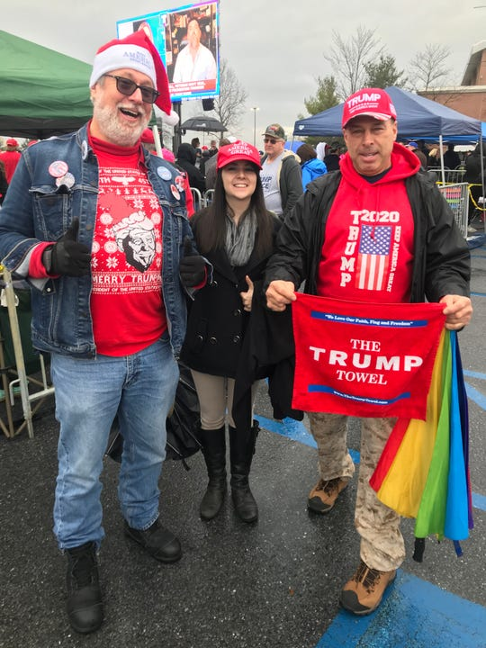 "From left, Edward X. Young, Christina Babbino and Michael Shapiro showed up early from New Jersey in advance of the Hershey, Pa., Trump rally. A large crowd of supporters waited in line outside Giant Center, hours before the president was expected to take the stage for a ""Keep America Great"" rally on Tuesday. As turmoil raged in Washington, D.C., Trump fans called the impeachment inquiry ""a sham,"" ""a joke"" and ""a disgrace to the nation."""