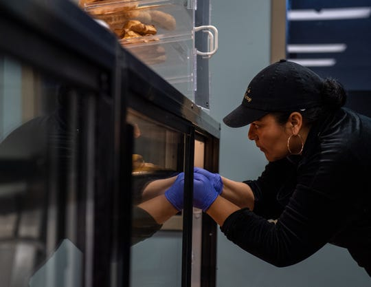 Stefania Reyes, slides in a tray filled with fresh bread for customers at The Village Bakery & Deli on Dec. 06, 2019.