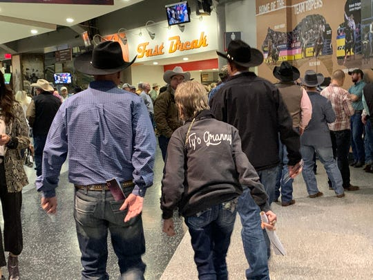 Peggy Harris, middle, grandmother of tie-down roper Ty Harris, heads into the Round 5 performance of the National Finals Rodeo Dec. 9, 2019, at the Thomas & Mack Center in Las Vegas.