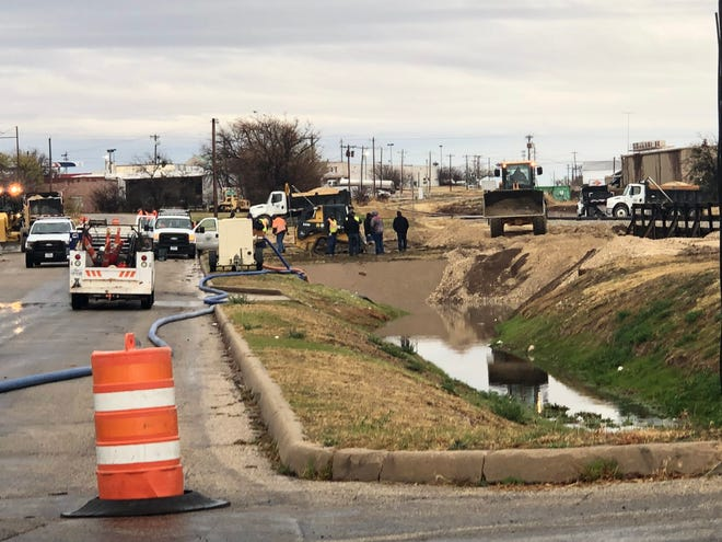 City of San Angelo crews work to repair berms after a sewer line break sent sewage into the Concho River on Dec. 10, 2019.