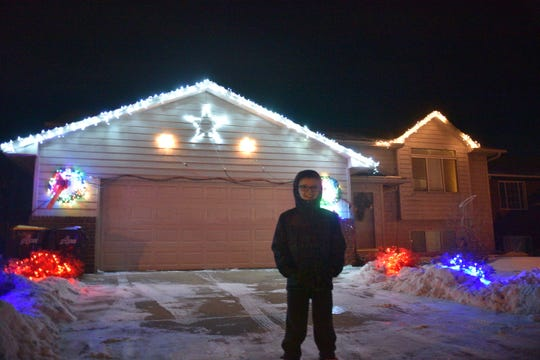 Jacob Richards stands in front of the Christmas lights display he's programmed to play along with music.