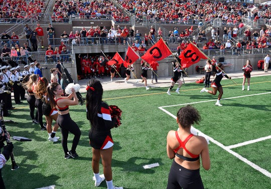 St. Cloud State cheerleaders lead their team onto the field for a 2015 game at Husky Stadium in St. Cloud.