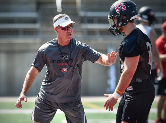 St. Cloud State head coach Scott Underwood talks with a player during practice Wednesday, Aug. 8, 2018, at Husky Stadium in St. Cloud.