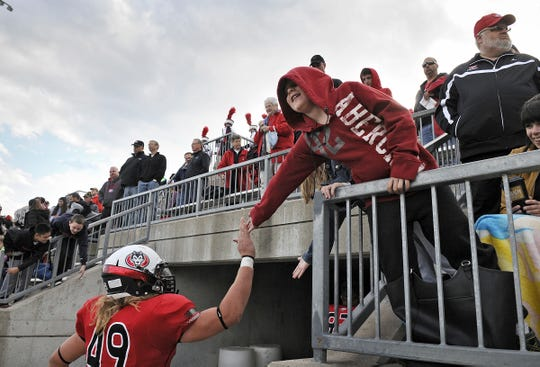 A young fan congratulates St. Cloud State University players as they leave the field after a game in 2014 against Wayne State (Nebraska) at Husky Stadium. The Huskies won 43-20.