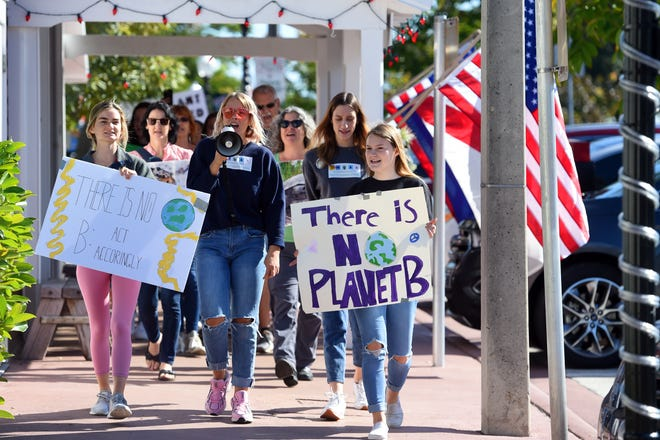 Maggie Mesoley (from left), 17, Kayla Keating, 18, and Abbie Nauss, 17, lead a march down Flagler Avenue on Friday, Dec. 6, 2019, as part of the U.S. Youth Climate Strike, a national grassroots organization raising awareness about climate change. Organizers from December's event applauded the city's efforts Monday to put climate change at the forefront in 2020.