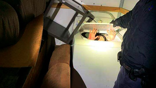 This photo from U.S. Customs and Border Protection shows hands held up by a person or people hiding in a washing machine, among 11 Chinese nationals found by agents inside a moving truck stopped Saturday while entering the U.S. from Mexico near San Diego.