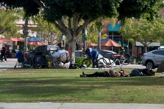 A small group of people, some of whom are homeless, spend the morning Tuesday in Plaza Park in downtown Oxnard.