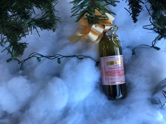 A bottle of wine from Woodland Trail Winery in Oconto County sits under a Christmas tree display at its new Rib Mountain store, Wine Time. The store opened on Dec. 7, 2019.