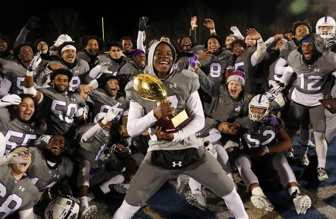 New Rochelle's Tariq Benjamin (7) dances with the gold ball trophy as he and his New Rochelle teammates celebrate their victory over Carmel in the Section 1 championship at Mahopac High School Nov. 9, 2019.