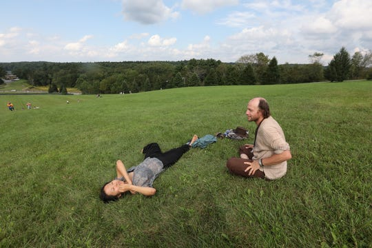 Louis West and Hein Jeong relax at the original Woodstock site during Woodstock's 50th anniversary at the Bethel Woods Center for the Arts Aug. 17, 2019.