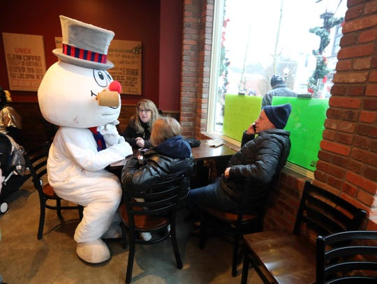 """After a parade and Christmas Tree lighting ceremony were cancelled due to unsafe conditions caused by rain and snow, Frosty the Snowman warmed up at the Tazzo coffee shop in Armonk Dec. 1, 2019. The 10th annual Frosty Day in Armonk was curtailed due to the unsafe weather conditions. The festival started out with children's activities, train rides in Wampus Brook Park, dancing and music, and other winter activities. The famous winter song Frosty the Snowman was written in 1950 by Walter """"Jack"""" Rollins and Steve Nelson, the latter of whom lived in Armonk at the time of the song's writing."""