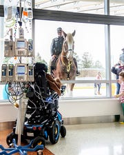 Kaden Morrison waves to New Castle County Police's mounted unit from inside Nemours/Alfred I. duPont Hospital for Children on Friday, Dec. 6, 2019.