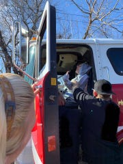 JJ Paxton is lifted into the cab of a fire truck by members of the Delaware Pagans motorcycle group at their annual Christmas Party for kids.