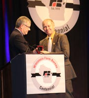American Farm Bureau Vice President Scott VanderWal presents retiring Wisconsin Farm Bureau President Jim Holte with a token of appreciation during the organization's centennial celebration and annual meeting Dec. 8 at Wisconsin Dells.