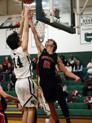Crooksville's Caden Miller tries to block a shot against Fisher Catholic's Josh Burke, left, during their game on Monday in Lancaster. Fisher won, 61-53, to stay unbeaten.