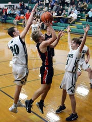 Crooksville's Caden Sparks goes up for a shot against Bryson Vogel, left, and Alex Bronden, of Fisher Catholic, on Monday in Lancaster. The Irish won, 61-53 to stay unbeaten.