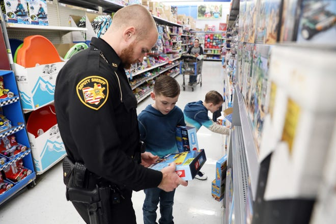 Muskingum County Sheriffs Office Deputy Jeremy Archer shops with brothers Eijah and Luke Walters during Shop With a Cop on Monday at Walmart in Zanesville.