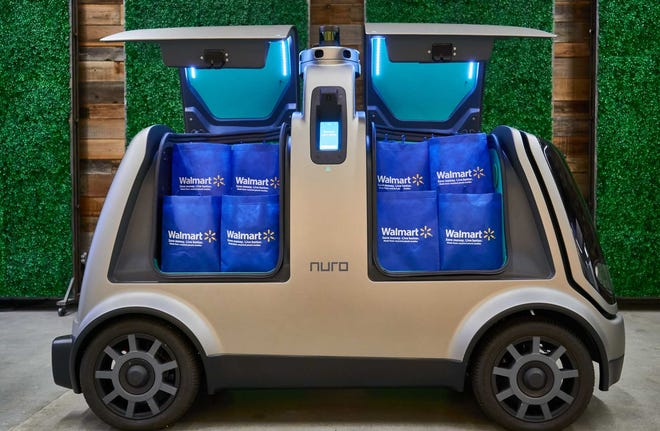 A Nuro self-driving vehicle carrying Walmart grocery bags.