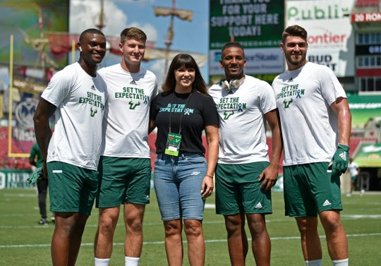 Rape survivor Brenda Tracy and University of South Florida football players show support for her nonprofit, Set the Expectation, dedicated to preventing sexual assault.