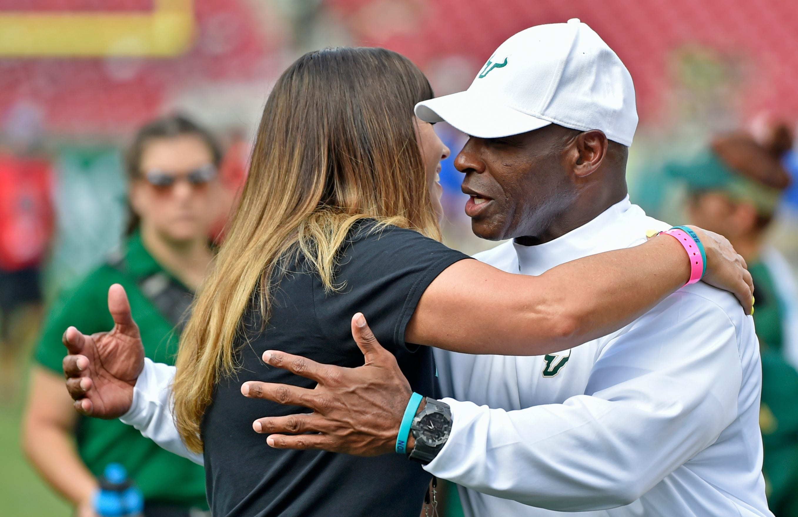 Brenda Tracy gives a pre-game hug to University of South Florida head coach football Charlie Strong on Sept. 28, 2019, in Tampa, Florida.