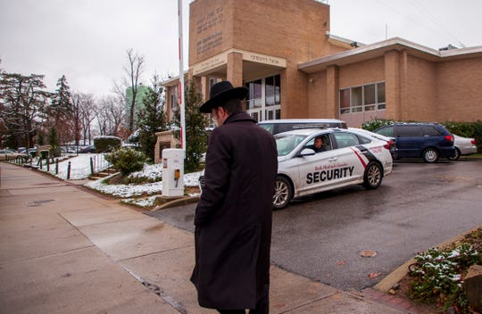 A man walks in front of the Yeshiva Beth Medrash Govoha as a security vehicle stands at one of the gates of the school in Lakewood, NJ, on Dec. 11, 2019.
