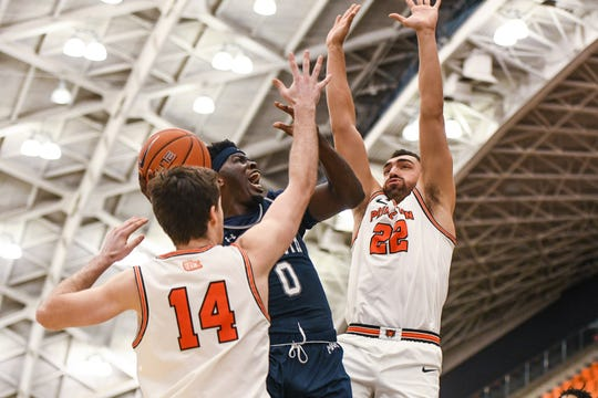 Monmouth's Ray Salnave (0) drives between Princeton's Jerome Desrosiers (22) and Ethan Wright (14) during Monmouth's dramatic 67-66 win on Tuesday night at Jadwin Gym in Princeton.