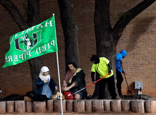 Zeek Ballejo rakes the leaves in front of a Nativity scene while Steve Barrera behind him does the same Wednesday in Hamlin. The men, who work for Ram Enterprises in Lubbock, were cleaning up the area in front of Vista Bank which had several green flags on display in support of the Hamlin Pied Pipers. The football team will face Stratford in the Class 2A Division II state semifinal at 6 p.m. Thursday in Plainview.