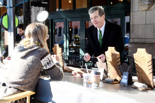 Governor Roy Cooper talks to artist Courtney Haney, of Rivers and Roots, as he visits with venders outside the Grove Arcade in Asheville December 11, 2019.