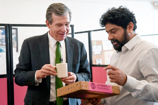 """Meherwan Irani shows Governor Roy Cooper the Spicewalla product that was chosen as one of """"Oprah's favorite things"""" in Asheville December 11, 2019."""
