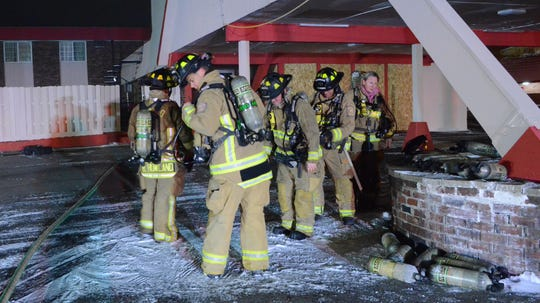 Firefighters line up to replace air tanks.