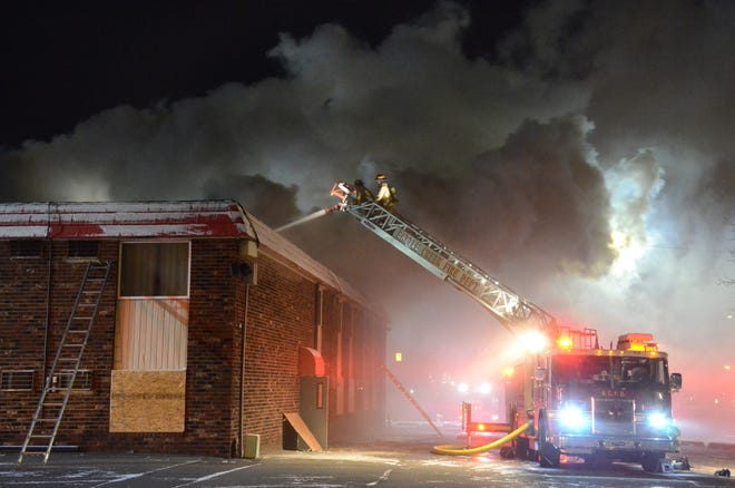 Firefighters attack a fire from above the roof of the Econo Lodge in Battle Creek in December.
