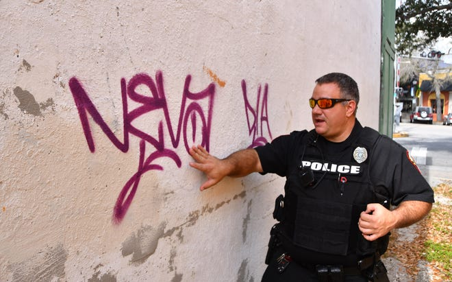 Melbourne Police Officer Ryan Allen points out graffiti on a wall facing a dirt alley near Henley Court in downtown Melbourne.