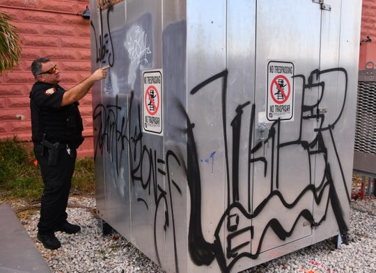 Melbourne Police Officer Ryan Allen examines graffiti defacing a railroad crossing electrical box near Continental Flambe in downtown Melbourne.