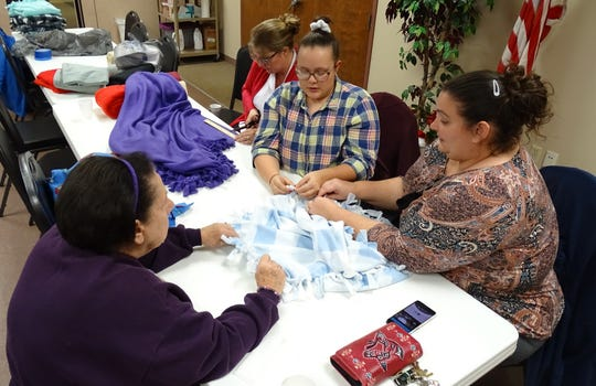 Salvation Army volunteers knot the fringes on fleece blankets on Tuesday at the Crawford County Council on Aging. From left are Toni Lind, Capt. Heidi Valdez, Miriam Keslig and Kylie Grau.